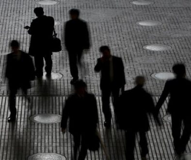 People walk at an office building at a business district in Tokyo