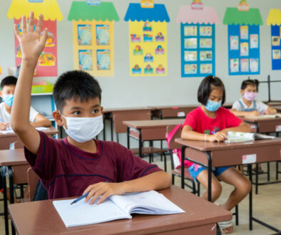 School kids wearing protective mask to Protect Against Covid-19,Group of school kids with teacher sitting in classroom and raising hands,Elementary school,Learning and people concept.