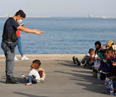 A policeman talks with children as migrants disembark from Migrant Offshore Aid Station ship Topaz Responder in the Sicilian harbour of Augusta