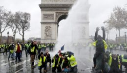 FILE PHOTO: Protesters wearing yellow vests, a symbol of a French drivers' protest against higher diesel taxes, stand up in front of a police water canon at the Place de l'Etoile near the Arc de Triomphe in Paris